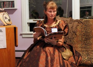 Volunteer Sheila Robinson wears her 1864 dress and reads the newest publication of the PEIGS: Confederation Connections: Genealogies of the PEI Fathers of Confederation.